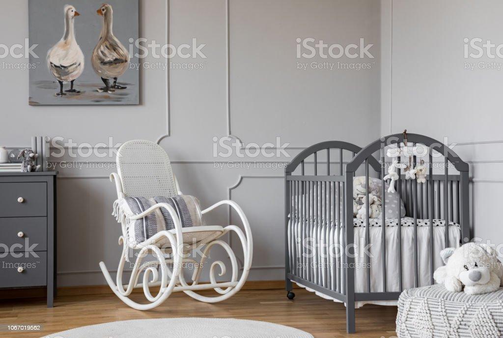photo libre de droit de fauteuil a bascule blanc avec loreiller a cote du berceau en bois dans la chambre de bebe elegant avec affiche du canard sur le mur banque d images