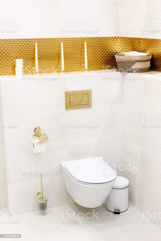 white toilet in a toilet with gold trim stock photo download image now istock