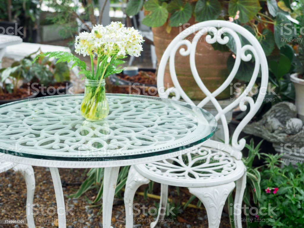 https www istockphoto com photo white wrought iron table with white flower in vase on glass top and chair vintage gm1249954201 364404182