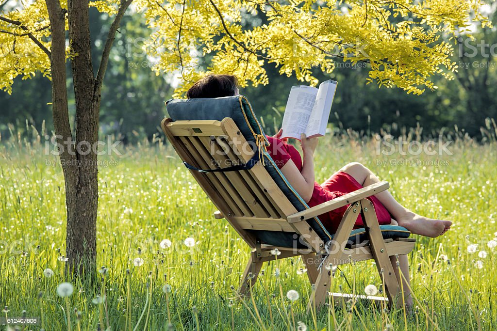 Woman Lying Outdoors In Deck Chair Reading Book Stock