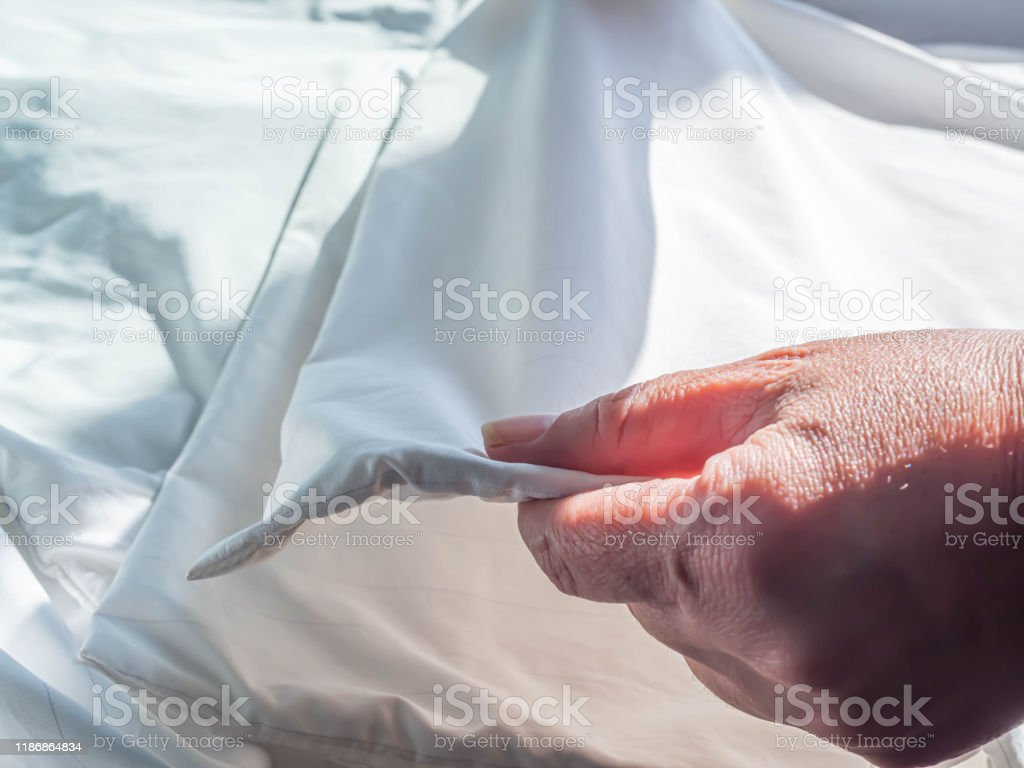 https www istockphoto com photo woman s hand folding zippered dust mites pillow cover on wrinkle white bed cover on gm1186864834 335021755