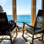A Woman Sits Next To An Empty Rocking Chair Facing An Ocean View Stock Photo Download Image Now Istock