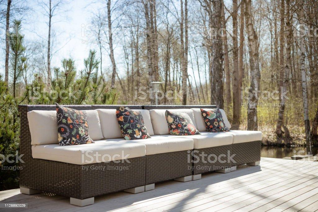 photo libre de droit de chaise de salon de jardin en bois avec coussin patio de jardin moderne avec sofa en rotin confortable espace detente a lexterieur grande terrasse patio avec meubles