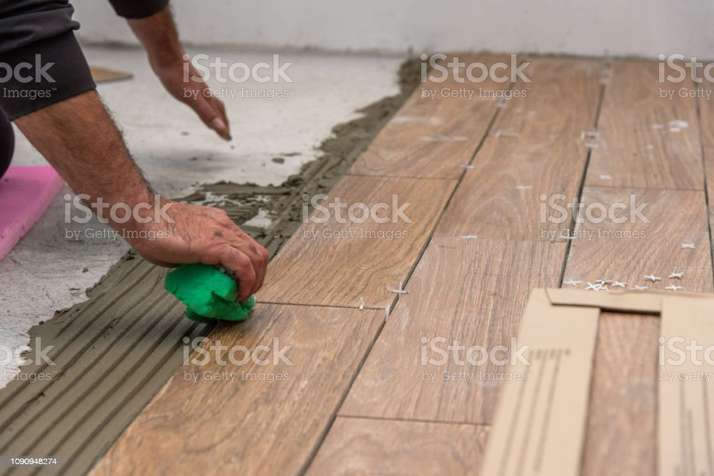 https www istockphoto com photo worker placing ceramic floor tiles on adhesive surface leveling with rubber hammer gm1090948274 292651612