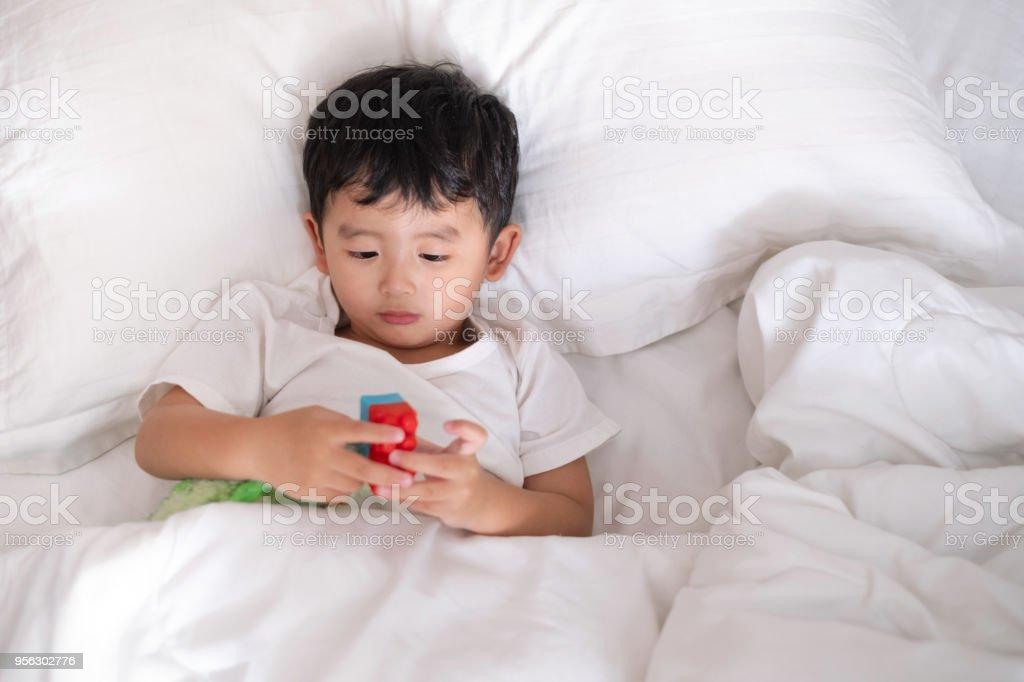 https www istockphoto com fr photo 3 ans vieux malades peu ou maladie asian boy c3 a0 domicile sur le lit triste enfant pose gm956302776 261102842