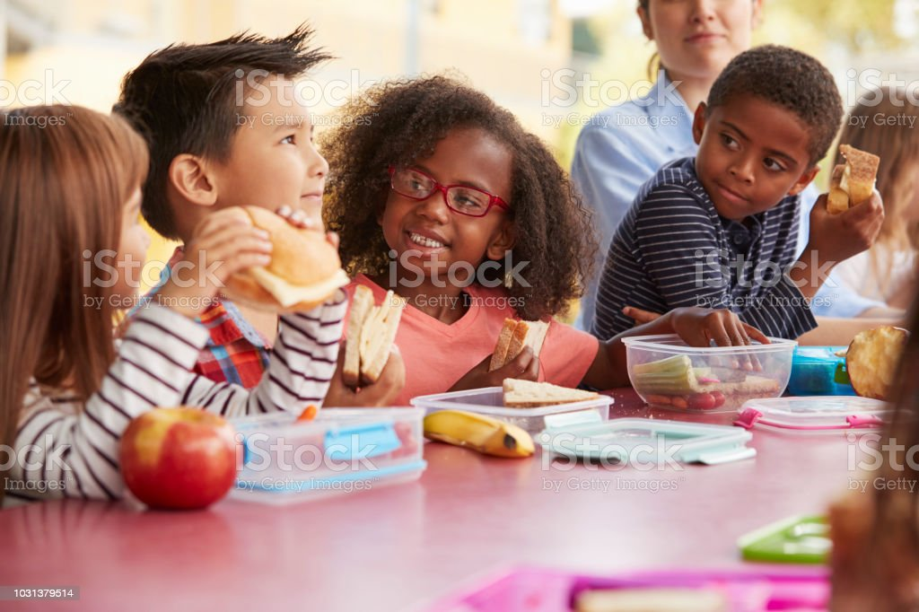 Young School Kids Eating Lunch Talking At A Table Together Stock Photo - Download Image Now - iStock