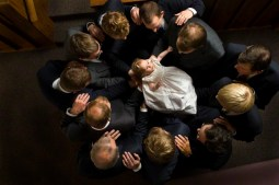 Eleven priesthood holders stand in a circle with a baby girl in their arms, giving her a blessing.