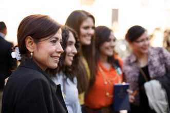 A brown-haired woman in a black dress jacket, standing in a group with other women outside the Conference Center.