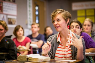 A young woman speaks up in a seminary classroom full of young men and young women, with her scriptures open on her desk.