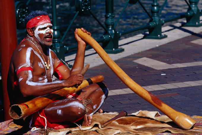 Australian Aboriginal busker playing didgeridoo in central city.