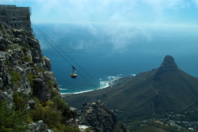 Cable car descending from Table Mountain, Lion's Head in background.