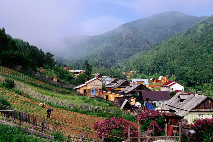 Houses in valley & villagers working in Garden in Listvyanka village on Lake Baikal.