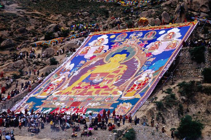 Pilgrims attending annual celebration of hanging of huge thangka, Drepung Monastery.