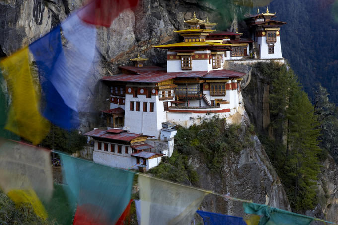 Taktshang Goemba or Tiger's Nest Monastery, perched on a steep cliff above the floor of Paro Valley, with fluttering prayer flags.
