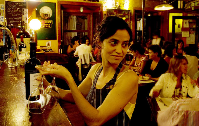 Waitress with wine bottle and two glasses preparing to attend table inside Cafe Buenos Aires restaurant, Baixa (downtown) district.