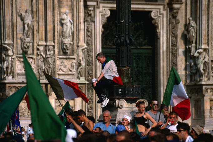 Soccer fans wearing and waving Italian flags on the Piazza del Duomo