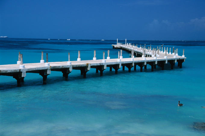 The white of a Cancun pier cuts through the turquoise waters of the Caribbean.