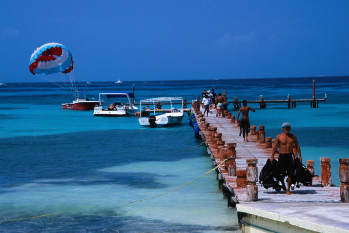 A parasailer takes off over visitors to the resort town of Cancun.