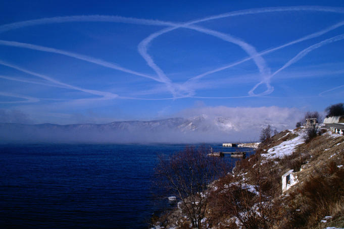 A stream of aeroplane smoke patterns the sky over Lake Baikal at Listvyanka.