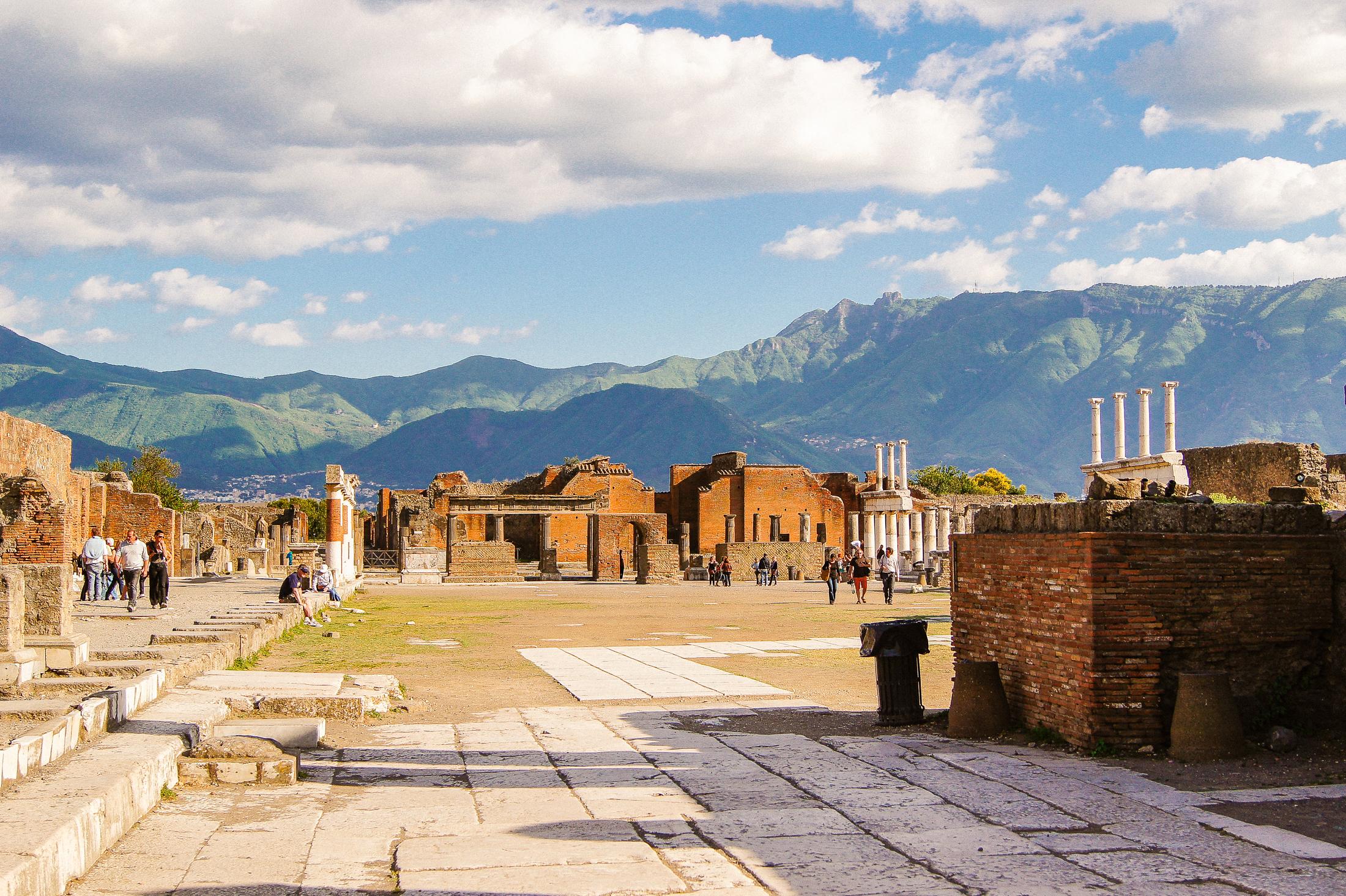 En stor öppen yta, mitt i Pompeji, med berg i bakgrunden.