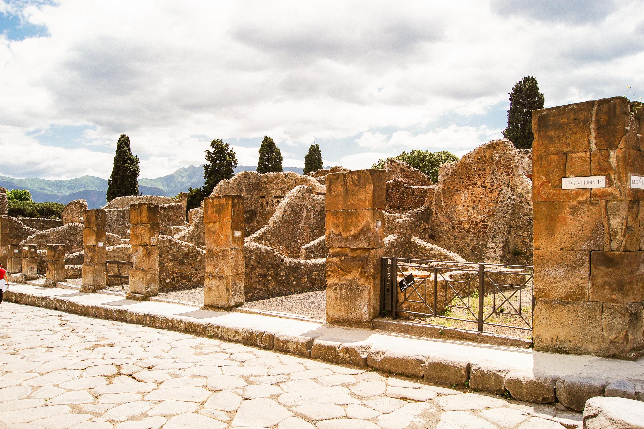 Stenruiner vid sidan av en stengata i Pompeji.