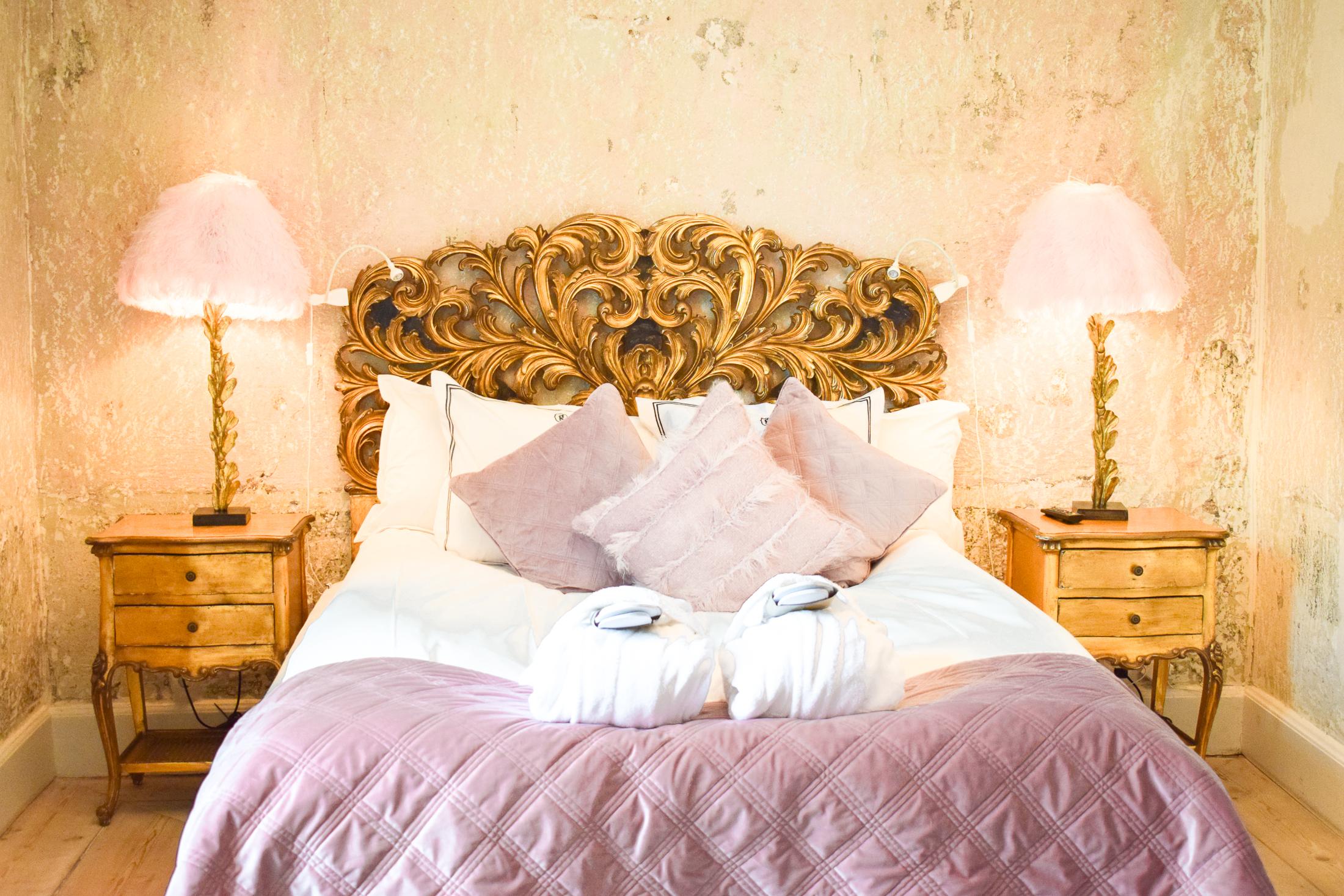 deluxrum med rosa inredning och guldig sängram.