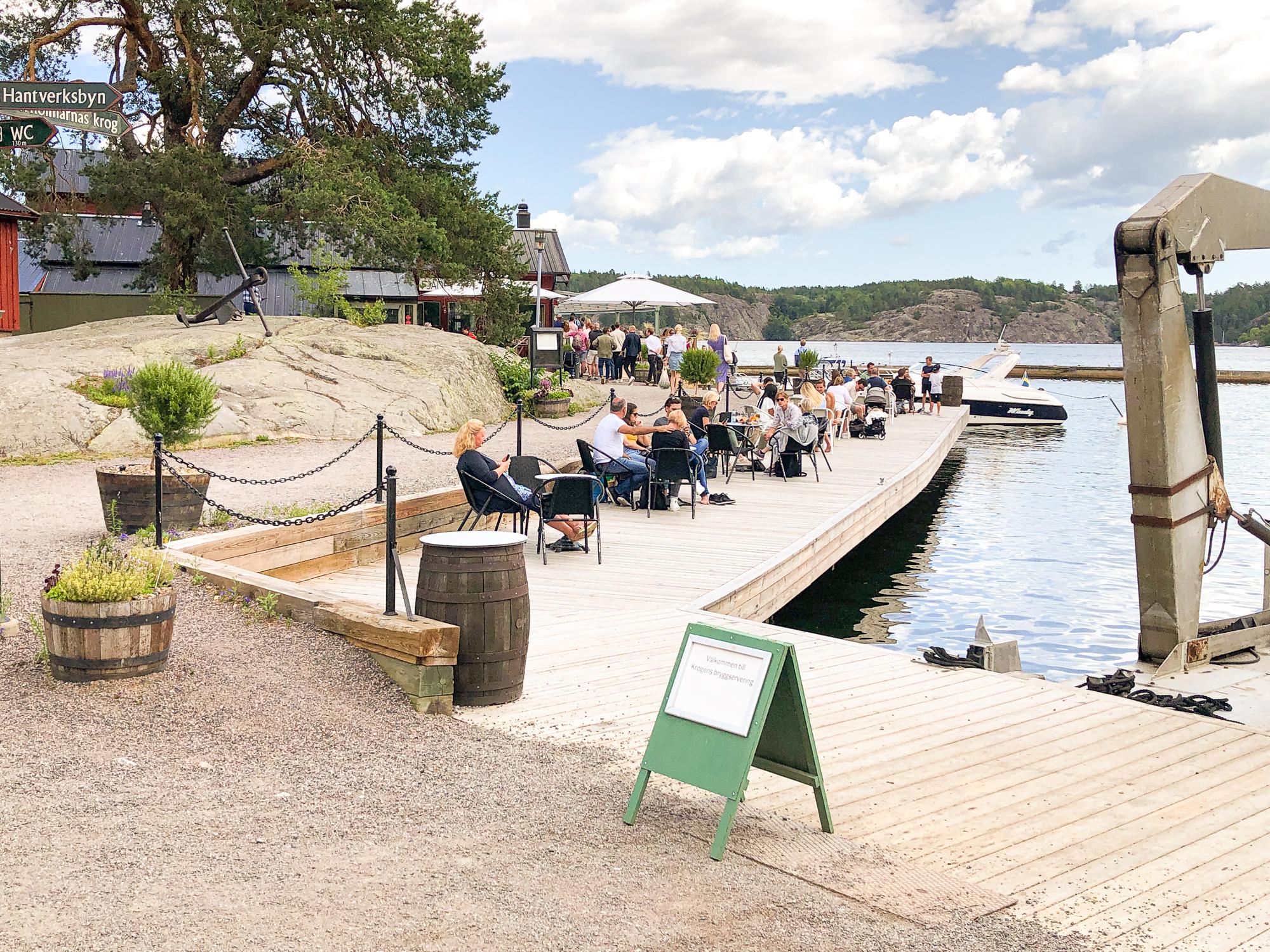 folk sitter på stolar på en träbrygga vid vattnet på fjäderholmarna.