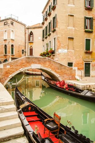 två stilla gondoler i kanalen, framför en stenbro.
