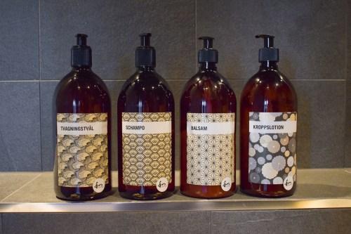 fyra flaskor med tvål, schampo, balsam och lotion.