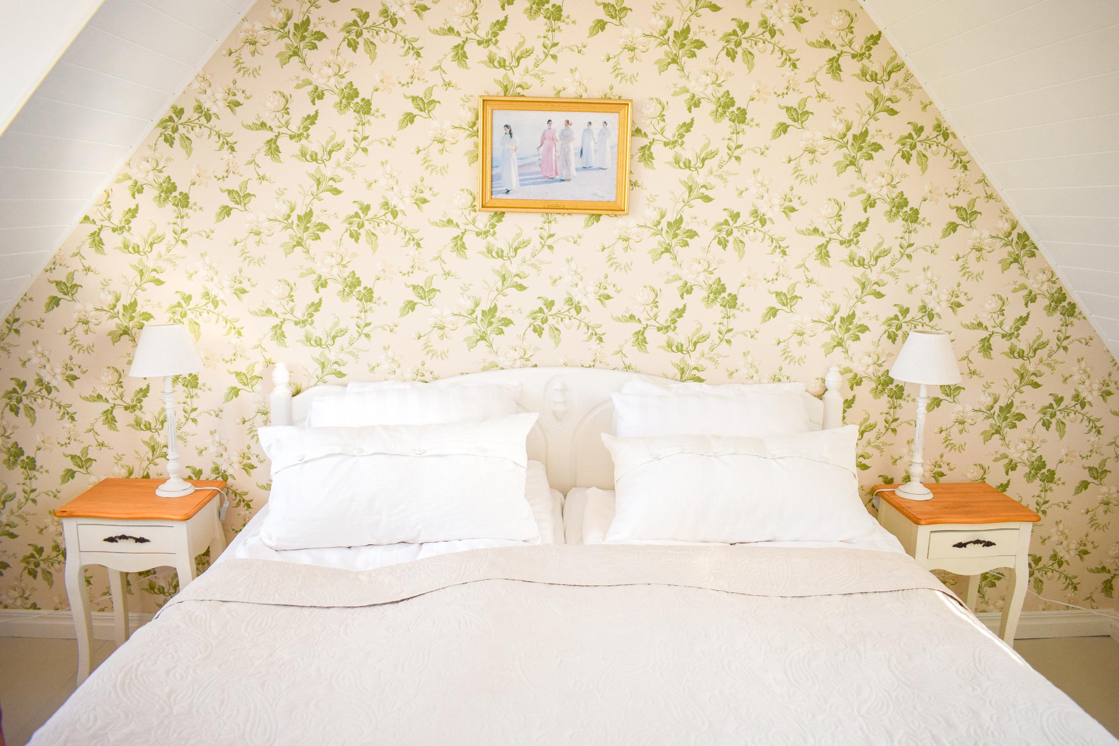 säng och sängbord på boende på österlen.