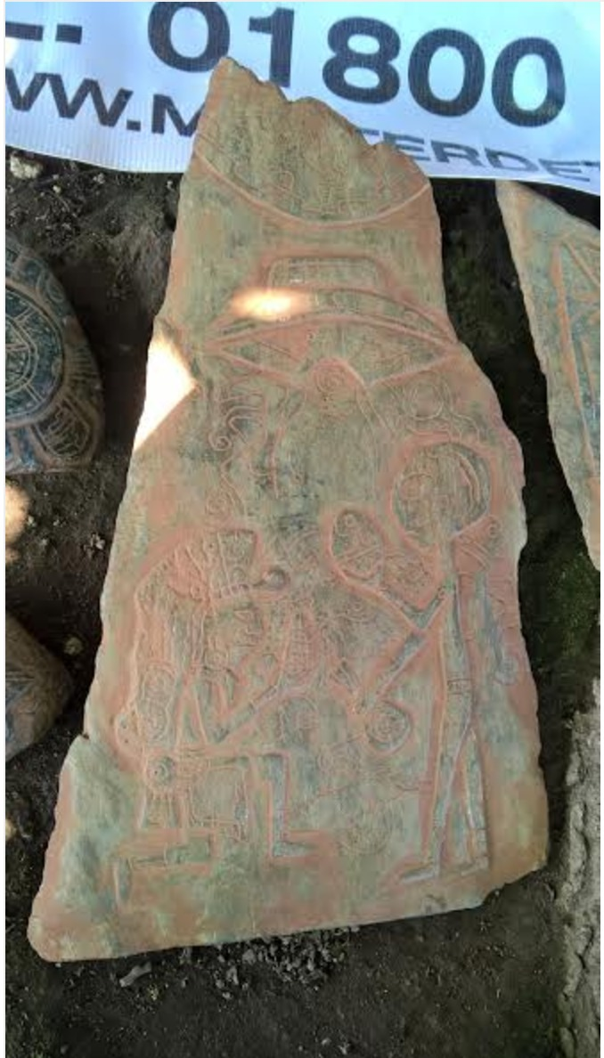 A prehispanic hierarch hands an ear to an alien and a saucer or ship drawn on the stone above.