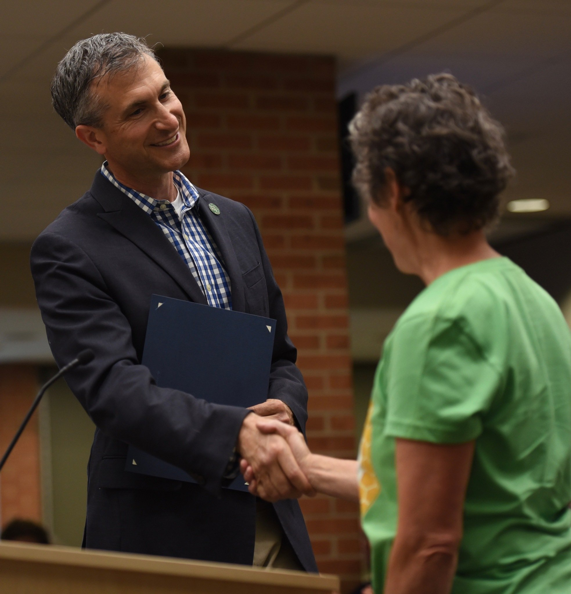 Mayor Christopher Taylor shakes hands with Eileen Dickinson after reading a proclamation in honor of National Pollinator Week on June 6, 2016.