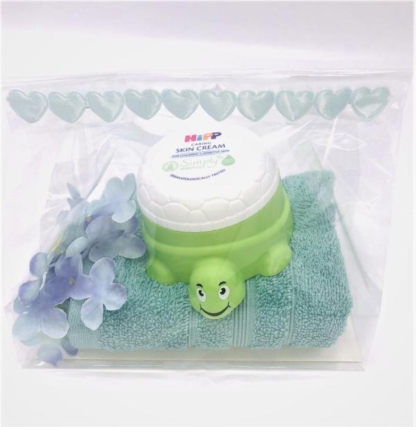 Presentpåse: Frottehandduk, hudkräm, blomma