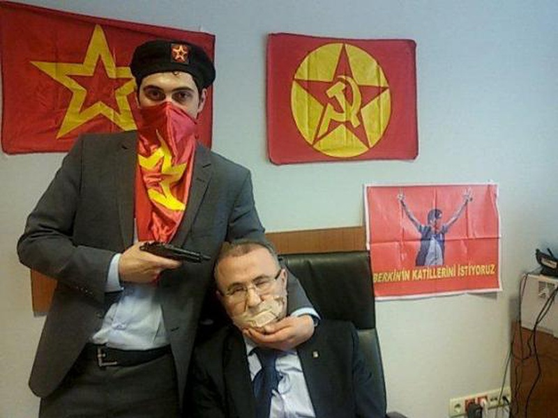 A gunman poses with Prosecutor Mehmet Selim Kiraz with a gun on his head after being taken hostage in his office in a court house in Istanbul March 31, 2015. REUTERS/HALKIN SESI TV/HANDOUT VIA REUTERS