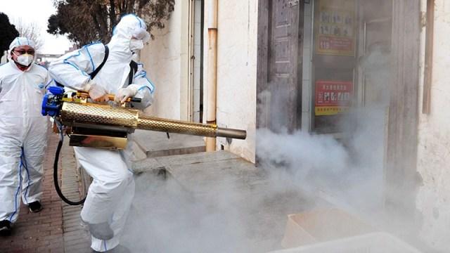 Wolontariuszka koronawirusa Qingdao w kombinezonie ochronnym dezynfekuje dzielnicę Qingdao w Chinach.