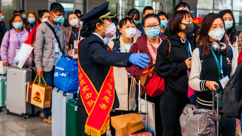 People in face masks queue with luggage, directed by an official in a face mask and gloves.