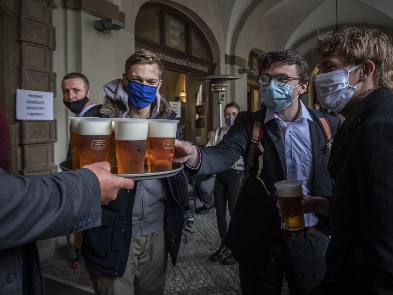 People drink beer at an outdoor seating section of a pub, as the Czech government lifted more restrictions.