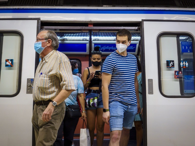 Passengers wear protective face masks as they alight a Metro train in Madrid.