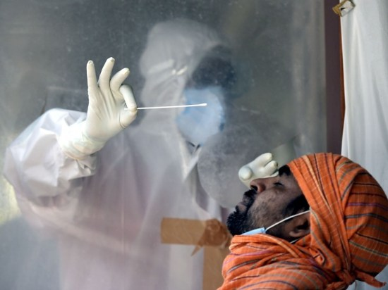 A health worker collects a swab sample from a man to test for coronavirus infection, New Delhi, India.