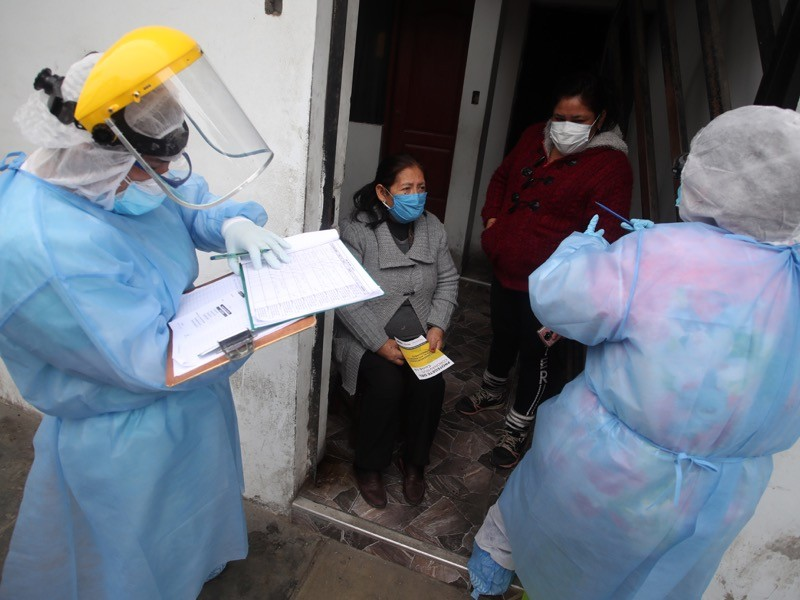 Doctors report to family members after taking a rapid test during a house-to-house coronavirus testing drive in Lima.