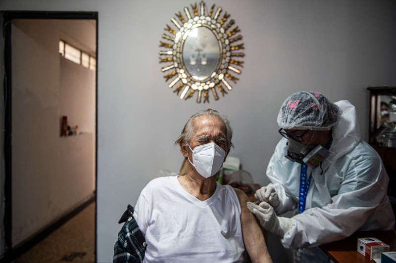 A health worker gives an older man a dose of the Pfizer–BioNTech COVID-19 vaccine