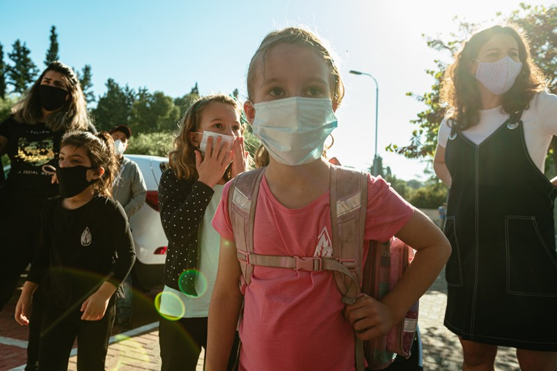 A group of children and adults wearing face masks.