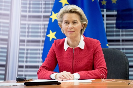Ursula van der Leyen seated at a desk in front of an EU flag.