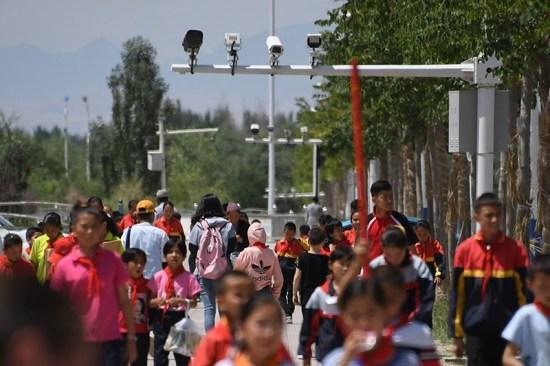 schoolchildren walking below surveillance cameras in China's western Xinjiang region.