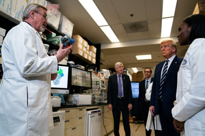 Barney Graham holds a molecular model as he speaks to Donal Trump and others during a tour of his lab