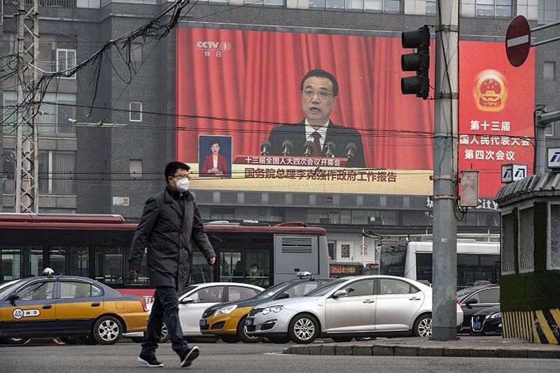 Un hombre pasa junto a una pantalla que muestra al primer ministro chino Li Keqiang hablando en el Congreso Nacional del Pueblo en Beijing.
