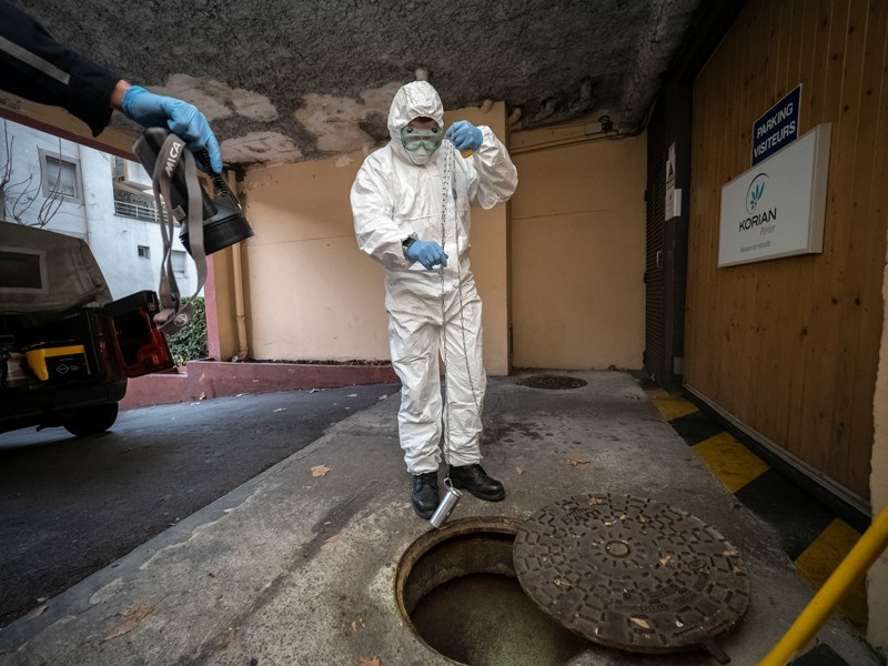 A firefighter in a protective suit takes samples of sewage from Marseille