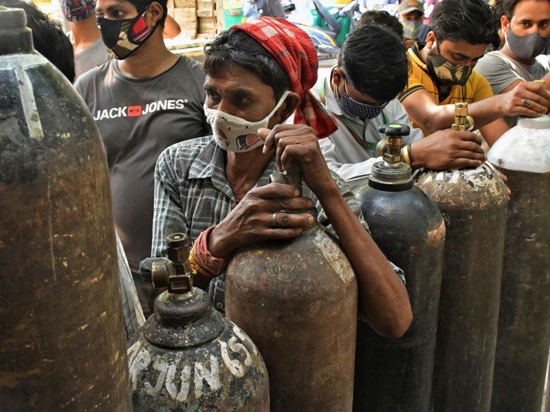 Masked people are waiting to refill their oxygen cylinders.