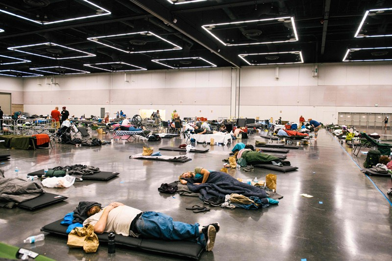 People sleep on mattresses on the floor of a large hall under ceiling fans at a cooling centre in Oregon during a heat wave