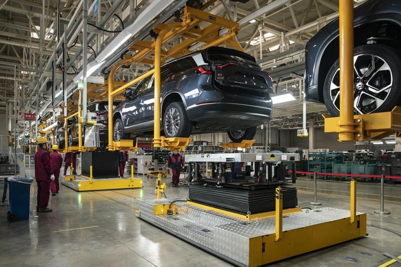 Los empleados instalan baterías en automóviles elevados en la línea de producción de una planta de producción de vehículos eléctricos en China